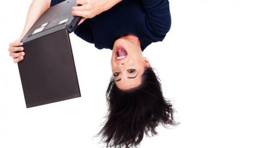 girl using laptop computer upside down